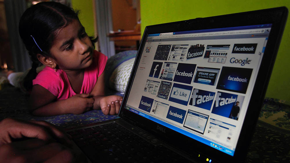 An Indian works on a laptop displaying Facebook logos, as a child watches in Hyderabad, India, Friday, May 18, 2012. Facebook's stock is set to begin trading on the Nasdaq Stock Market on Friday, the day after the world's definitive online social network raised $16 billion in an initial public offering that valued the company at $104 billion. (AP Photo/Mahesh Kumar A.)