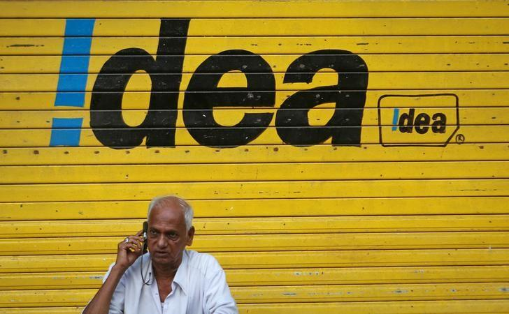 A man speaks on his mobile phone as he sits in front of a shop displaying the Idea Cellular Ltd's logo on its shutter in Mumbai, India, April 28, 2014. REUTERS/Danish Siddiqui/File Photo